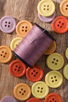 Bovenaanzicht van draadspoel met knopen en naai-naald