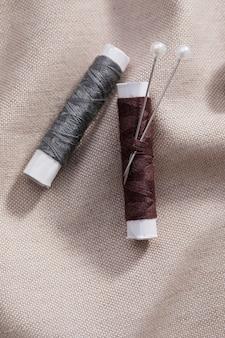 Bovenaanzicht van draadspoelen met naalden op textiel
