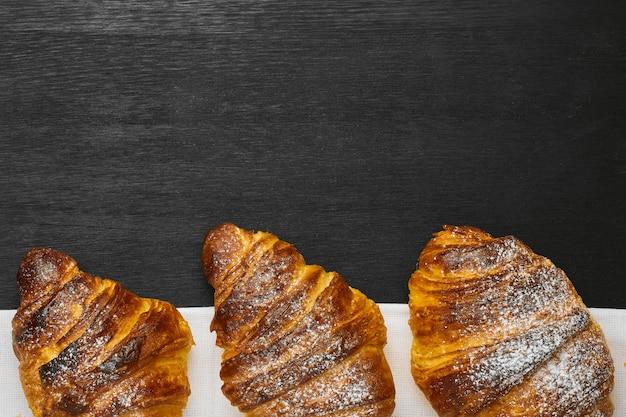 Bovenaanzicht van drie croissants op een zwarte achtergrond met kopie ruimte. levering van producten