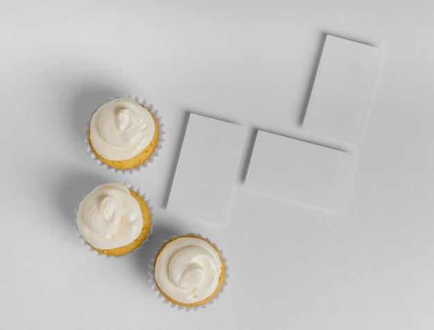 Bovenaanzicht van drie cupcakes met blanco kaarten