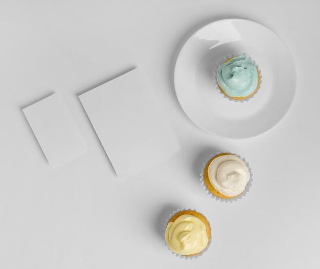 Bovenaanzicht van drie cupcakes op plaat met blanco kaarten