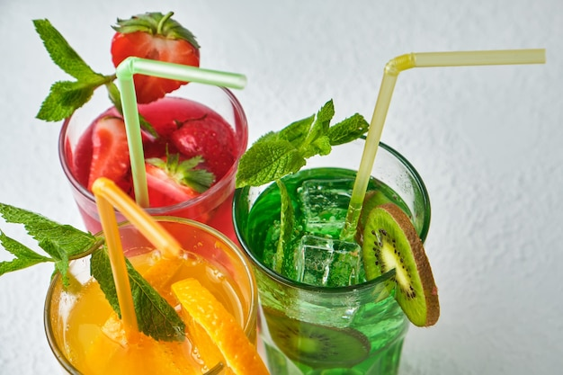 Bovenaanzicht van drie felgekleurde heerlijke koude limonadekaraffen van kiwi en sinaasappel en aardbei met munt op lichte ondergrond