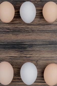 Bovenaanzicht van drie kippeneieren gerangschikt op een houten achtergrond met kopie ruimte