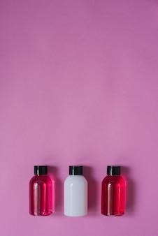 Bovenaanzicht van drie kleine flesjes wit en karmozijn en lichaams- en haarverzorgingsproducten bovenop een roze achtergrond
