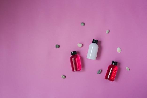 Bovenaanzicht van drie kleine flesjes wit en karmozijnrood en lichaams- en haarverzorgingsproducten, zeekiezelstenen bovenop een roze achtergrond. cosmetica voor toeristen
