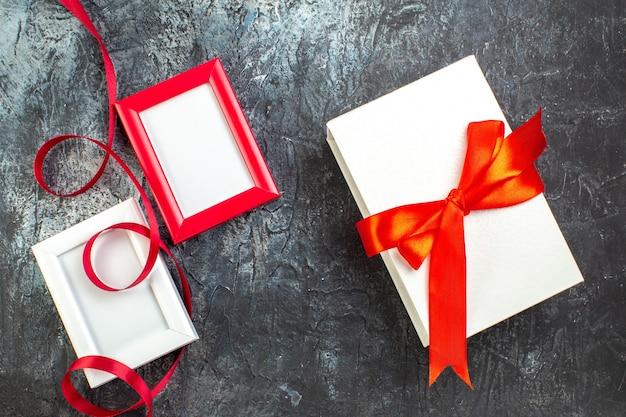 Bovenaanzicht van drie lege fotolijsten en cadeau met lint op donker