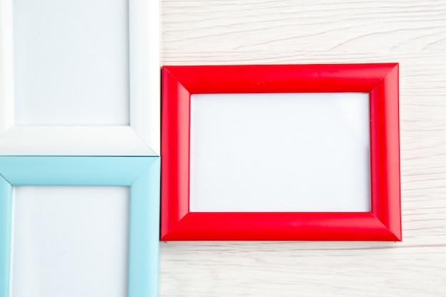 Bovenaanzicht van drie lege fotolijsten in verschillende kleuren op gestript