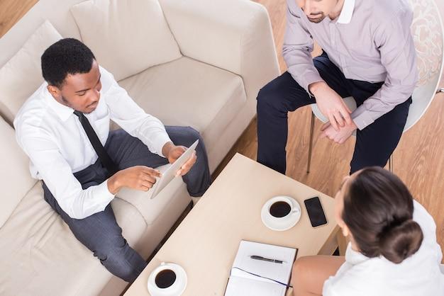 Bovenaanzicht van drie mensen uit het bedrijfsleven zitten aan de tafel.