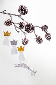 Bovenaanzicht van drie papieren koningen met dennenappels voor epiphany-dag