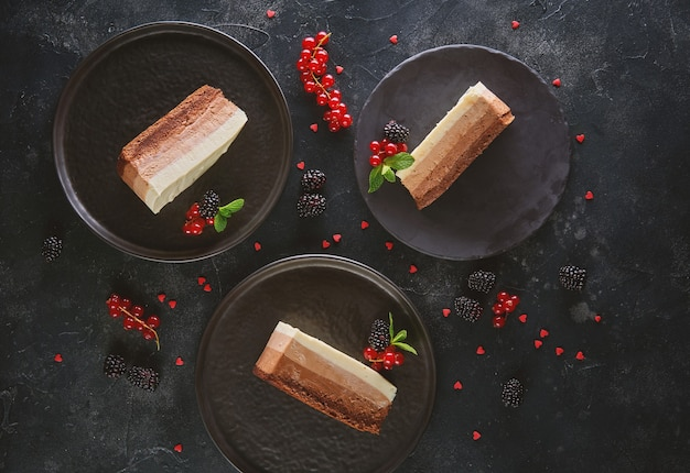 Bovenaanzicht van drie plakjes mousse cake op donkere achtergrond