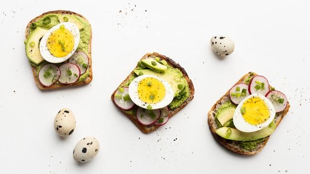 Bovenaanzicht van drie sandwiches met eieren en avocado