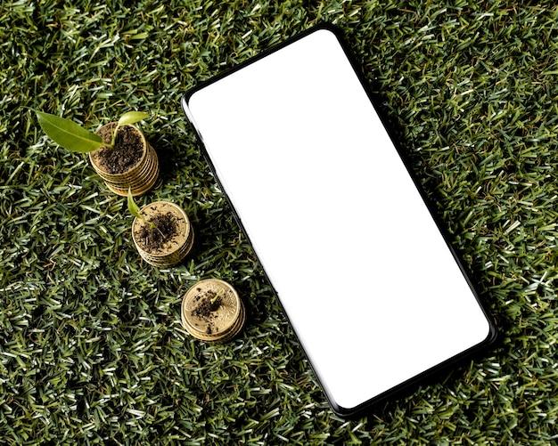 Bovenaanzicht van drie stapels munten op gras met smartphone
