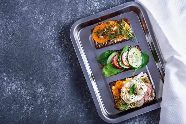 Bovenaanzicht van drie vegetarische toast met gepocheerde eieren, kwark, gele tomaten, radijs, komkommer, spinazie op dienblad op grijze achtergrond, gezonde snack concept