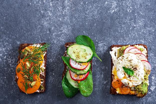 Bovenaanzicht van drie vegetarische toast met gepocheerde eieren, kwark, gele tomaten, radijs, komkommer, spinazie op grijze achtergrond