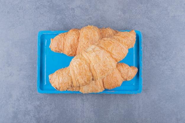 Bovenaanzicht van drie verse croissants op blauwe houten bord