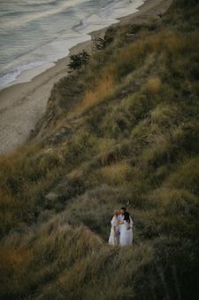 Bovenaanzicht van drie volwassen mensen die samen op de met gras begroeide heuvel knuffelen