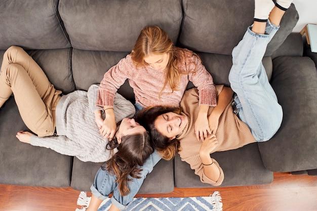 Bovenaanzicht van drie vriendinnen op de bank thuis