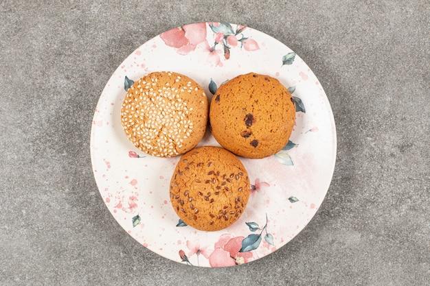 Bovenaanzicht van drie zelfgemaakte zoete koekjes op witte plaat.