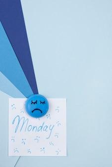 Bovenaanzicht van droevig gezicht met notitie en kopieer ruimte voor blauwe maandag