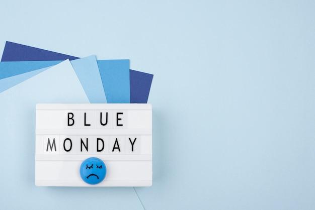Bovenaanzicht van droevig gezicht met papier en lichtbak voor blauwe maandag