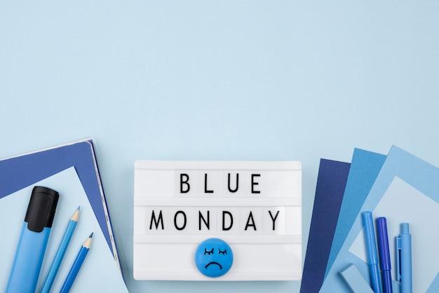 Bovenaanzicht van droevig gezicht met potloden en lichtbak voor blauwe maandag