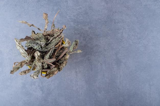 Bovenaanzicht van droge gezonde bladeren op grijs.