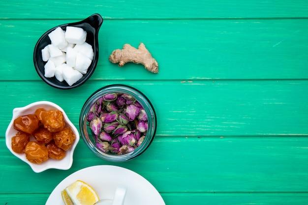 Bovenaanzicht van droge rozenknoppen in een glazen pot met gedroogde kersenpruimen, suikerklontjes en een kopje thee op groen hout met kopie ruimte