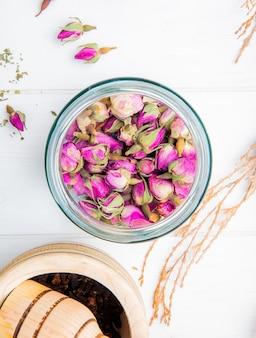 Bovenaanzicht van droge thee roos toppen in een glazen pot met zwarte peper in een houten vijzel op wit hout