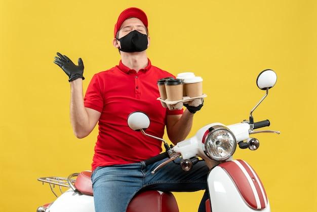 Bovenaanzicht van dromerige bezorger met uniform en hoed handschoenen in medische masker zittend op scooter met bestellingen