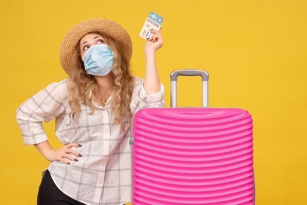 Bovenaanzicht van dromerige jonge dame met masker kaartje tonen en permanent in de buurt van haar roze tas