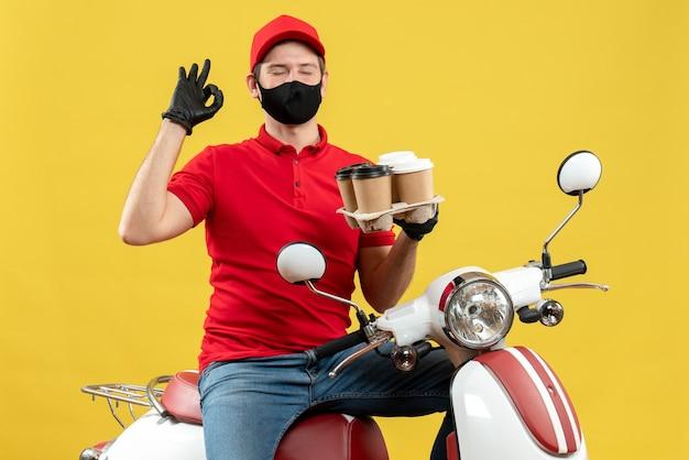 Bovenaanzicht van dromerige levering man met uniform en hoed handschoenen in medische masker zittend op scooter weergegeven: orders brillen gebaar maken