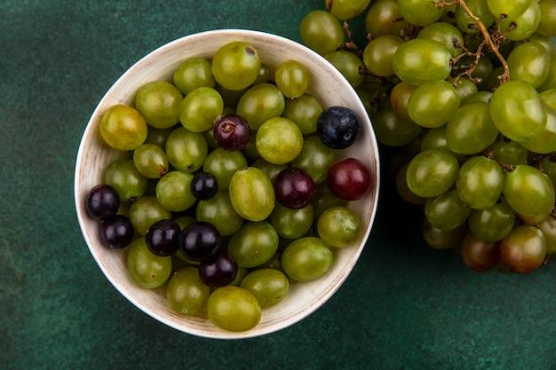 Bovenaanzicht van druiven bessen in kom en bos van druivenmost op groene achtergrond