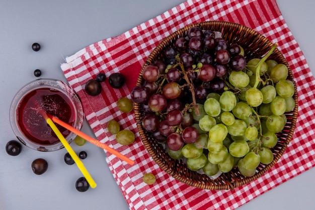 Bovenaanzicht van druiven in mand op geruite doek en glas druivensap op grijze achtergrond