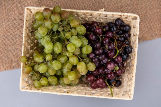 Bovenaanzicht van druiven in mand op zak op grijze achtergrond