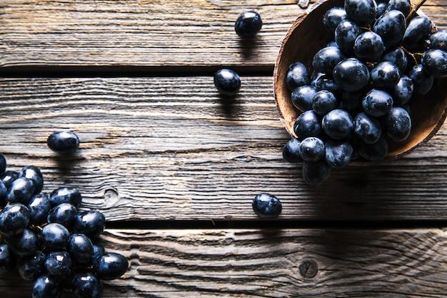 Bovenaanzicht van druiven in rieten mand op houten tafel. fruit