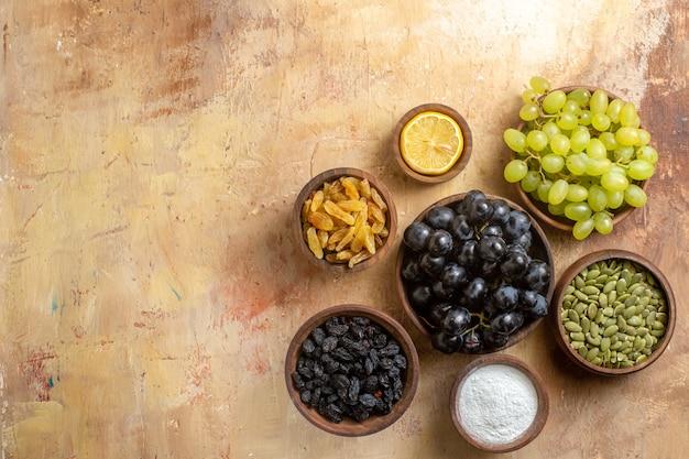 Bovenaanzicht van druiven kommen met trossen druiven rozijnen suiker citroen pompoenpitten