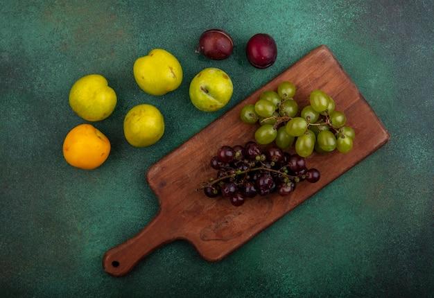Bovenaanzicht van druiven op snijplank met patroon van plukken en nectacot op groene achtergrond
