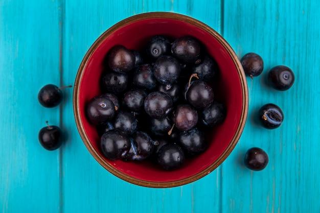 Bovenaanzicht van druivenbessen in kom en op blauwe achtergrond
