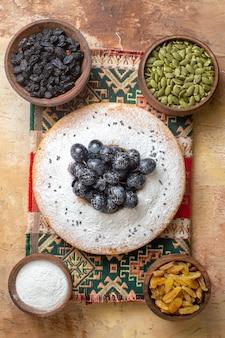 Bovenaanzicht van druivencake met druiven pompoenpitten suiker druiven rozijnen op het tafellaken
