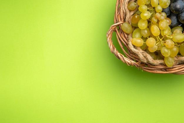 Bovenaanzicht van druiventrossen druiven in de houten mand op de groene achtergrond
