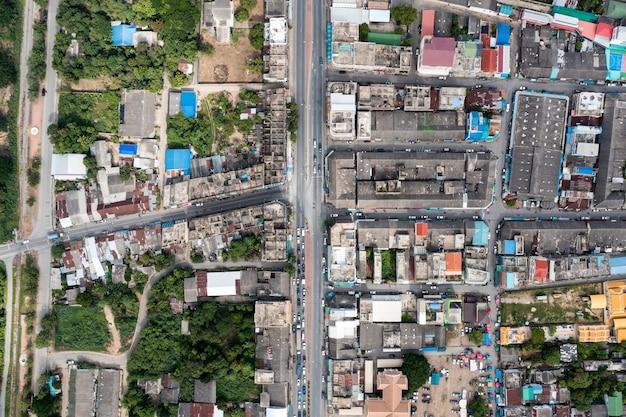 Bovenaanzicht van druk commercieel gebouw en woningen in landelijke buurt en verkeer op de weg in het district