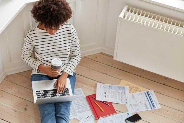 Bovenaanzicht van drukke ervaren verre werker toetsenborden op laptopcomputer, berekent de kosten