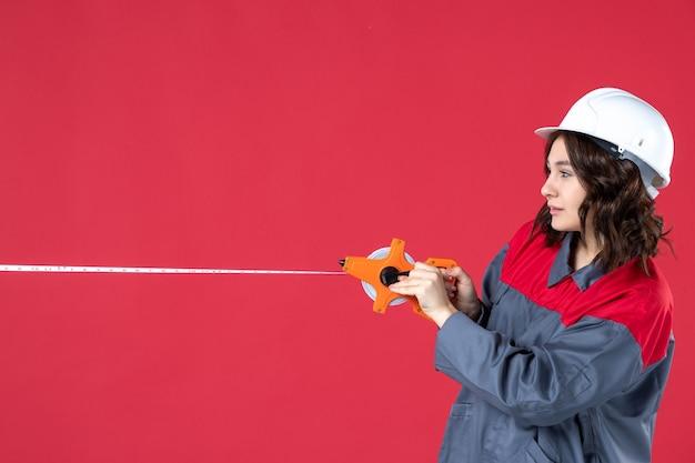 Bovenaanzicht van drukke lachende vrouwelijke architect in uniform met harde hoed opening meetlint op geïsoleerde rode achtergrond