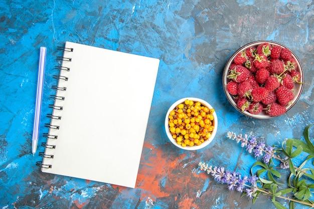 Bovenaanzicht van duindoorn in kom framboos kom een notitieboekje een pen op blauw oppervlak