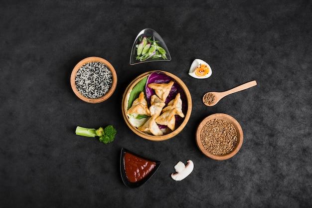 Bovenaanzicht van dumplings in steamers omgeven met sesam; saus; korianderzaden; broccoli en paddestoel op zwarte achtergrond