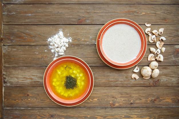 Bovenaanzicht van dushbara en champignonsoepen op houten bord