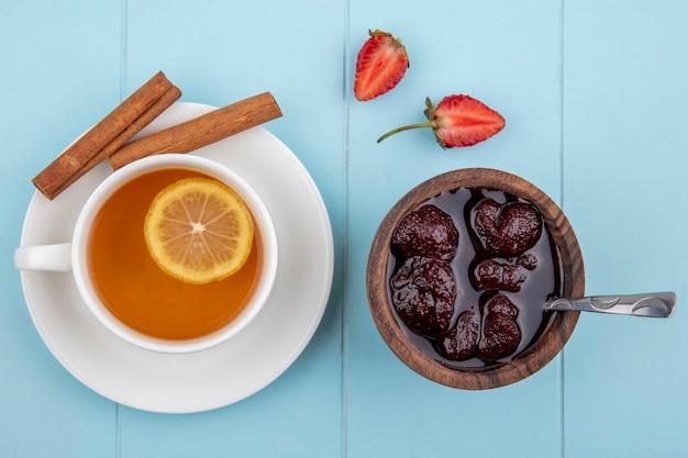 Bovenaanzicht van een aardbeienjam op een houten kom met theelepel met een kopje thee met kaneel op een blauwe achtergrond