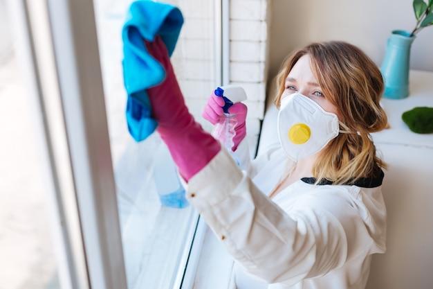 Bovenaanzicht van een aardige werkende jonge vrouw tijdens het schoonmaken van ramen in huis