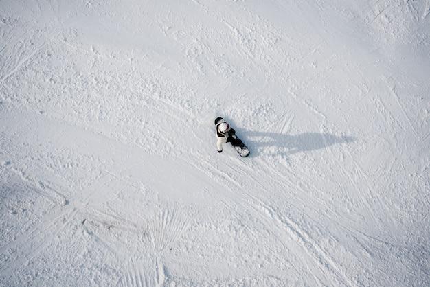 Bovenaanzicht van een actieve snowboarder in winter bergen.
