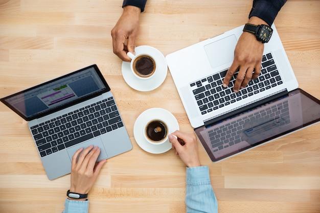 Bovenaanzicht van een afrikaanse man en een blanke vrouw die twee laptops gebruikt en samen koffie drinkt op houten tafel
